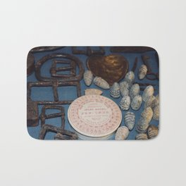 Belt buckles, iron musket bullets and perfume Bath Mat