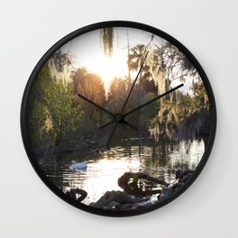 Mossy Trees Surround A Sun Reflected Lake With White Goose Wall Clock
