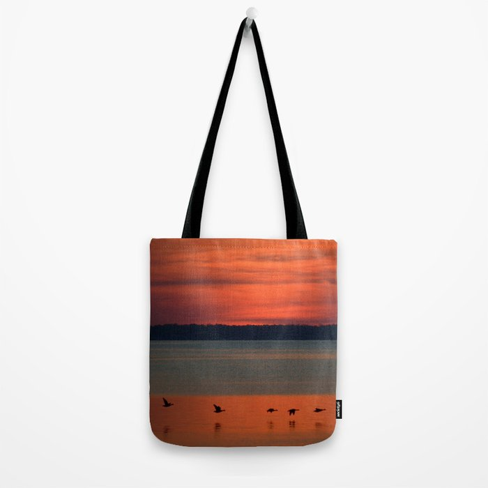 A flock of geese flying north across the calm evening waters of the bay Tote Bag