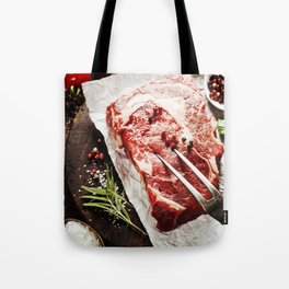 Raw beef steak with meat fork and ingredients on wooden background Tote Bag