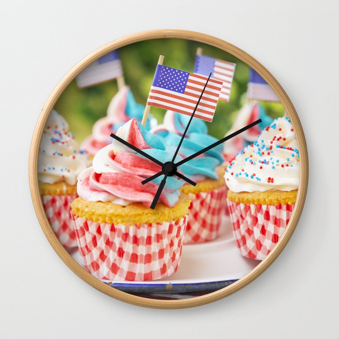 Cupcakes with red-white-and-blue frosting and American flags on outdoor table Wall Clock