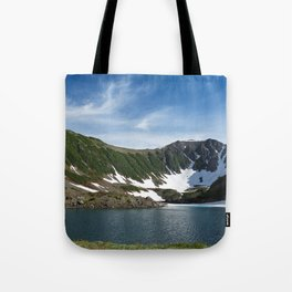 Stunning summer mountain landscape: Blue Lake, green forest on hillsides, blue sky on sunny day Tote Bag