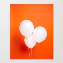 Three white balloons on orange backdrop Canvas Print