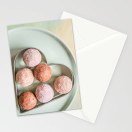 Golden delicious chocolate balls in heart shaped metallic cookie cutter on plate view from above Stationery Cards
