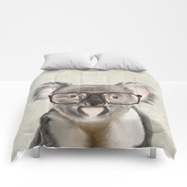 A baby koala with glasses on a rustic background Comforters