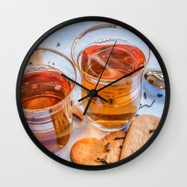 Black tea in two small tea glasses with heart shaped ginger cookies on pastel background Wall Clock