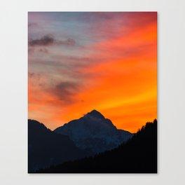 Stunning vibrant sunset behind mountain Canvas Print