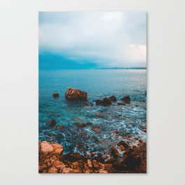 some rocks at sea on a cloudy background Canvas Print