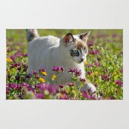 cat among wild flowers Rug
