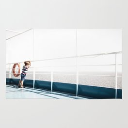 Child staring at the sea Rug