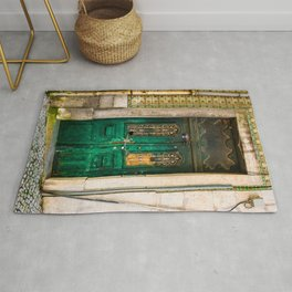 Old wooden door secured with chain and padlock. Wall with profusely decorated tiles. Rug