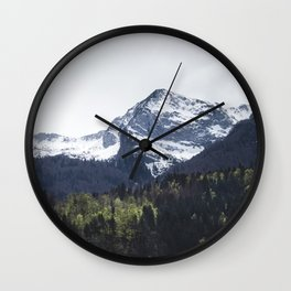Winter and Spring - green trees and snowy mountains Wall Clock