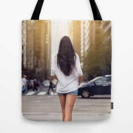 Beautiful girl with long legs walking around New York City street wearing jeans shorts. Rear view. Tote Bag