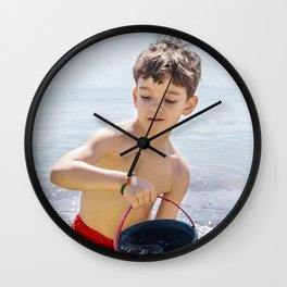 Young boy playing on a beach in French Riviera Wall Clock