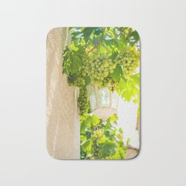 Bunch of grapes with green leaves in daylight Bath Mat