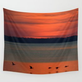 A flock of geese flying north across the calm evening waters of the bay Wall Tapestry