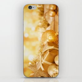 Christmas scene with gold baubles and gift, gold background iPhone Skin