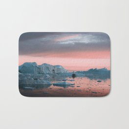 Boat in front of arctic icebergs during sunset Bath Mat