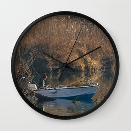 Fisherman on a boat by the river in the early morning Wall Clock