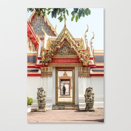 Lion statues guarding doorway to Wat Pho temple. Couple in the distance. Canvas Print