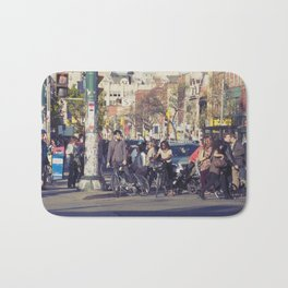 man in helmet stares wistfully across a busy intersection... Bath Mat