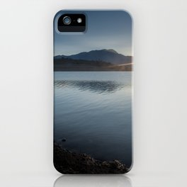 View of the sun rising over the mountaintop from across the lake iPhone Case