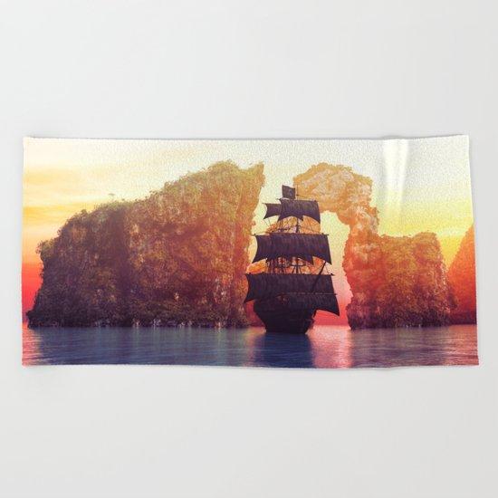 A pirate ship off an island at a sunset Beach Towel