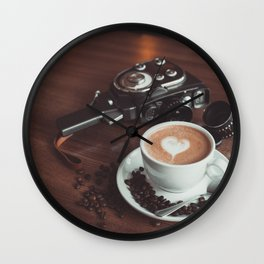 A cup of hot cappuccino placed on a table next to the old camera with lens and coffee beans Wall Clock