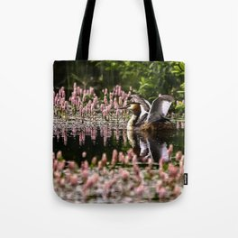 Grede stretching wings on pond, with flowering weed. Tote Bag