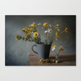 Chamomile flowers in a cup and in a vial Canvas Print