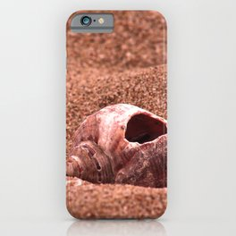 Seasnail shell with hole left on the sandy beach, nostalgic pink color summer photography iPhone Case
