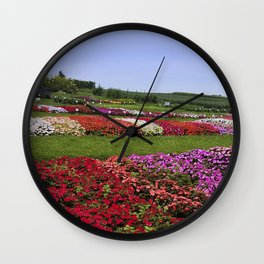Floral patchwork under a blue sky Wall Clock