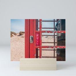 Old red telephone box on a sandy beach Mini Art Print