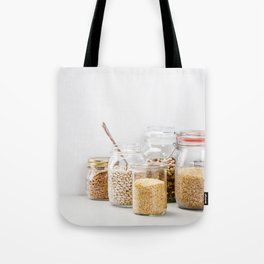 grains, legumes and nuts on concrete background Tote Bag
