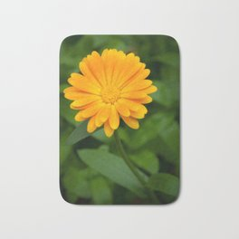 Yellow flower calendula officinalis and green leaves on background Bath Mat