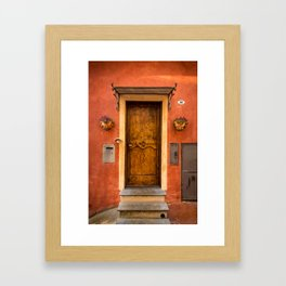 Wooden door of Tuscany with typical bright colors on its walls. Next to two small pots with flowers Framed Art Print
