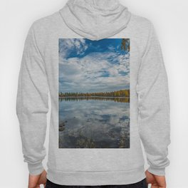 Picture of blue sky over autumn lake with stones in the water Hoody