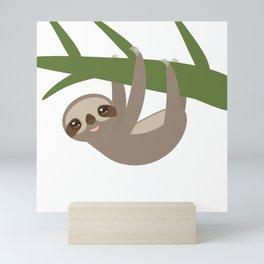 Three-toed sloth on green branch Mini Art Print