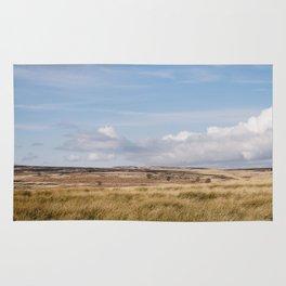 Blue sky and white clouds above sunlit moorland. Derbyshire, UK. Rug