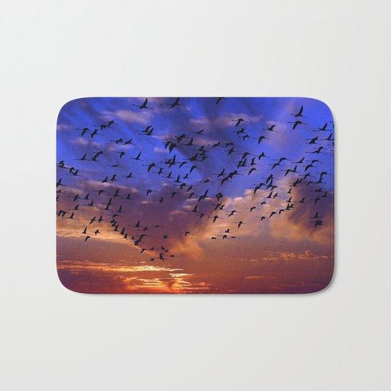 Flight of flamingos at sunset Bath Mat