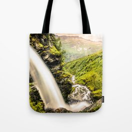 Waterfall down the cliff forming a river in nature Tote Bag