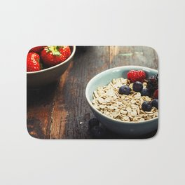 Bowls with cereals and fresh berries on wooden table Bath Mat