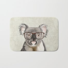 A baby koala with glasses on a rustic background Bath Mat