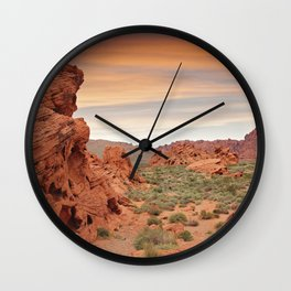 Desert mountains with open sandy area and small plants and rocks Wall Clock