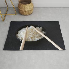 Rice bowl with Chinese chopsticks on dark background Rug