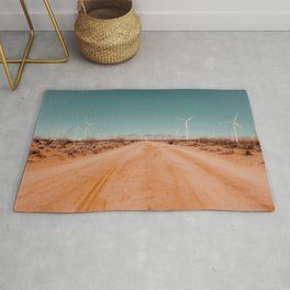 Wind turbine in the desert with sandy road at Kern County California USA Rug