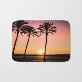 Orange bright sunset at the beach between palms Bath Mat