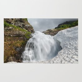 Summer landscape: mountain waterfall falling into snowfield Rug