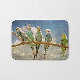 Parakeets perched on a branch againts a cloudy blue sky Bath Mat