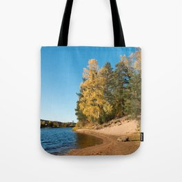 River with sandy shore with trees in autumn colors on a sunny day Tote Bag